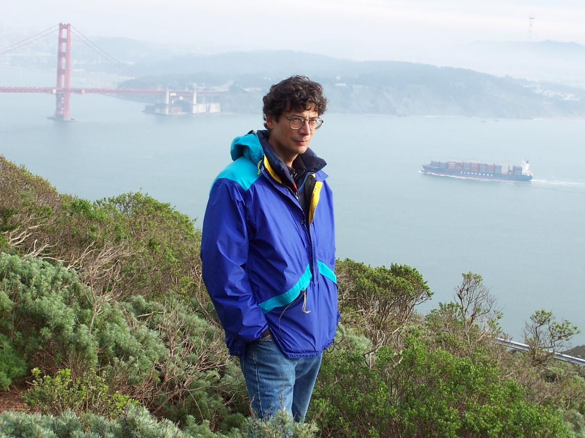 Man in blue jacket standing on hill overlooking Golden Gate Bridge