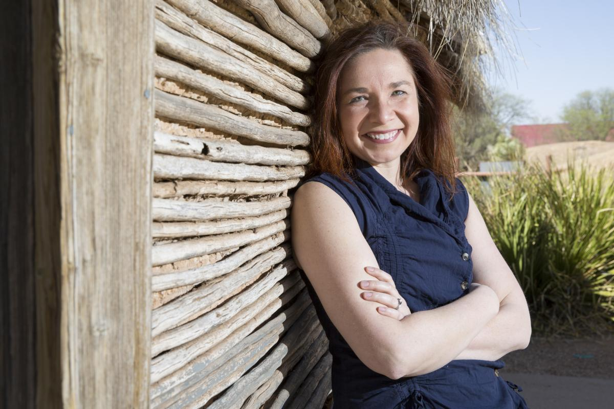 Katharine Hayhoe, a young brunette woman, leans against the wall of a wooden shed and smiles