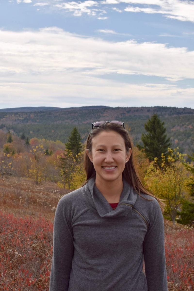 Head and shoulders picture of woman standing on mountain with red and yellow fall colors in the background