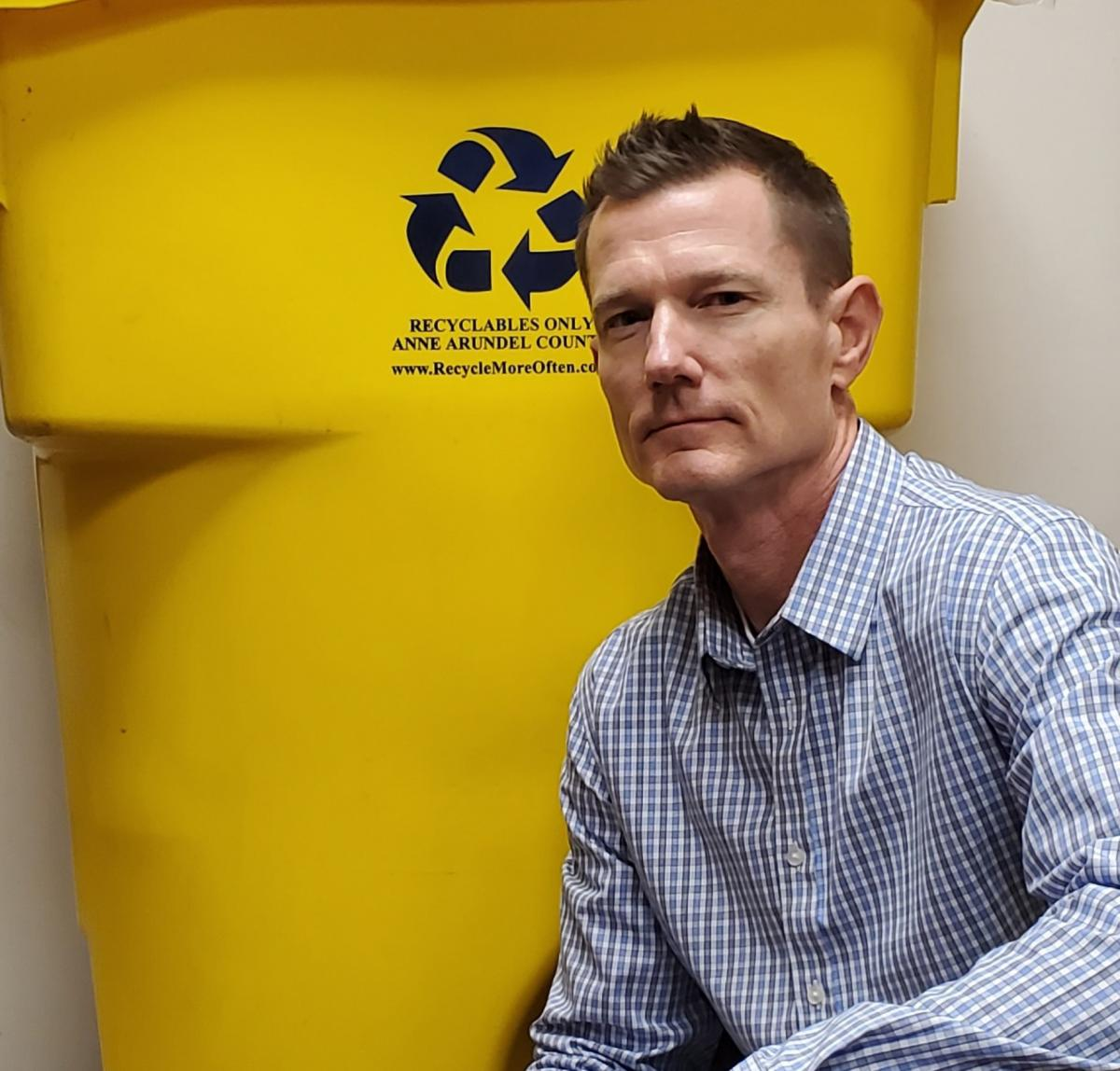 Man kneeling beside yellow recycling cart