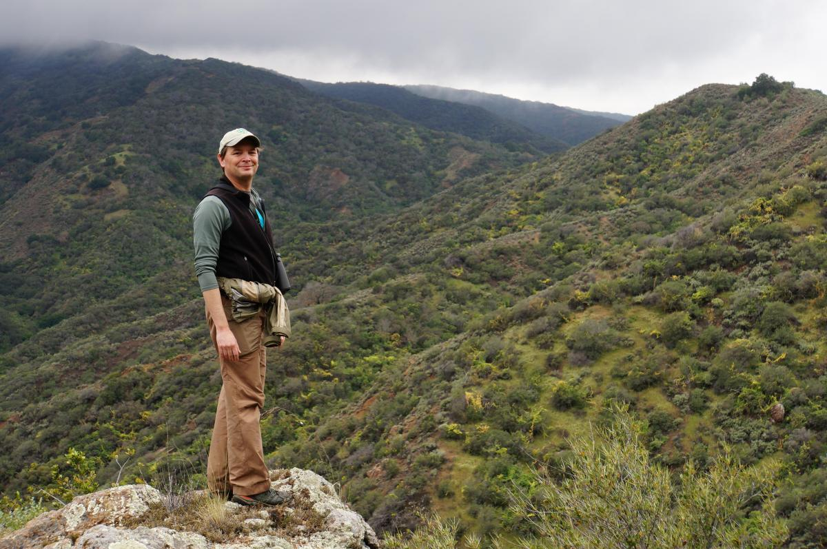 Man standing on rocky ledge in a misty mountain range