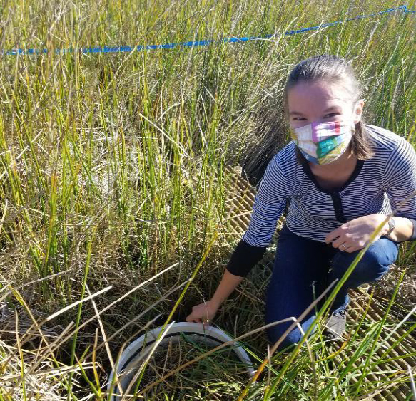 Young woman kneeling in grassy wetland wearing a multicolored face mask