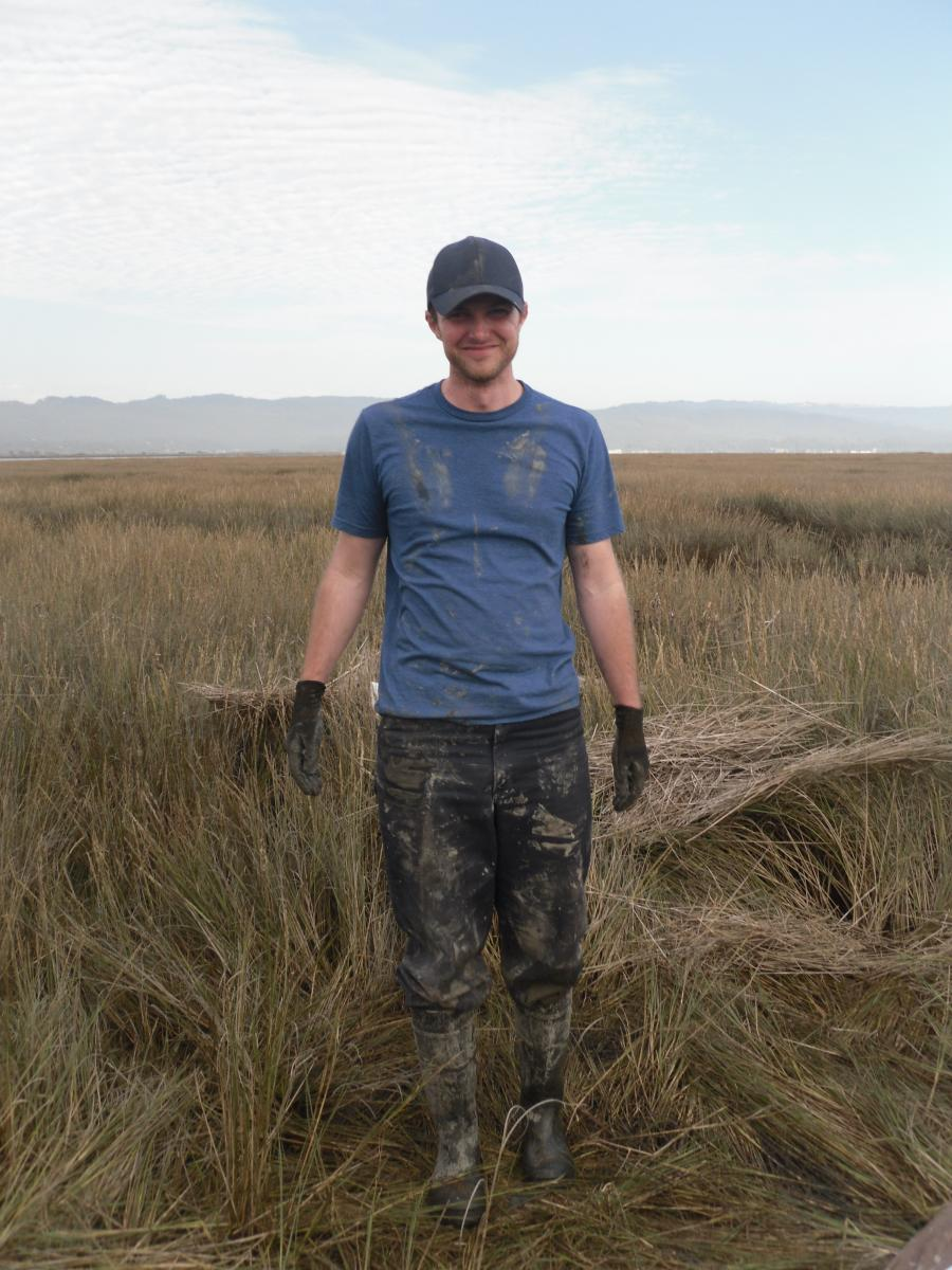 Man standing in wetland in muddy clothes