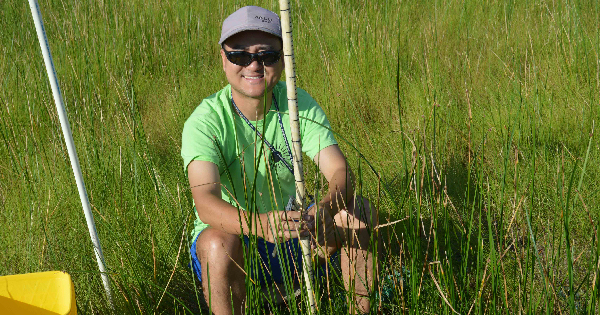 Young man in green T-shirt sitting in a marsh with a measuring stick
