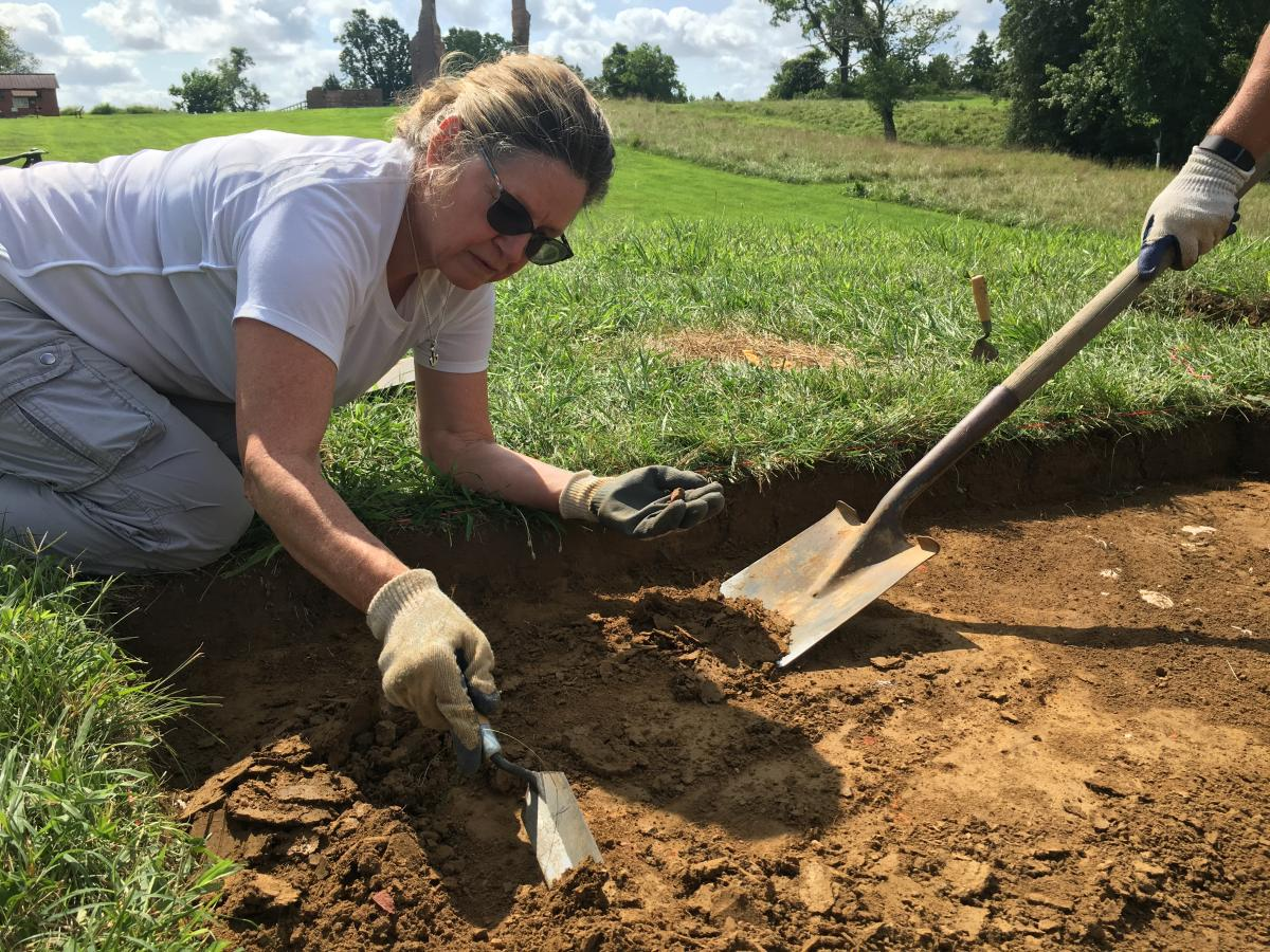Woman digging in soil pit