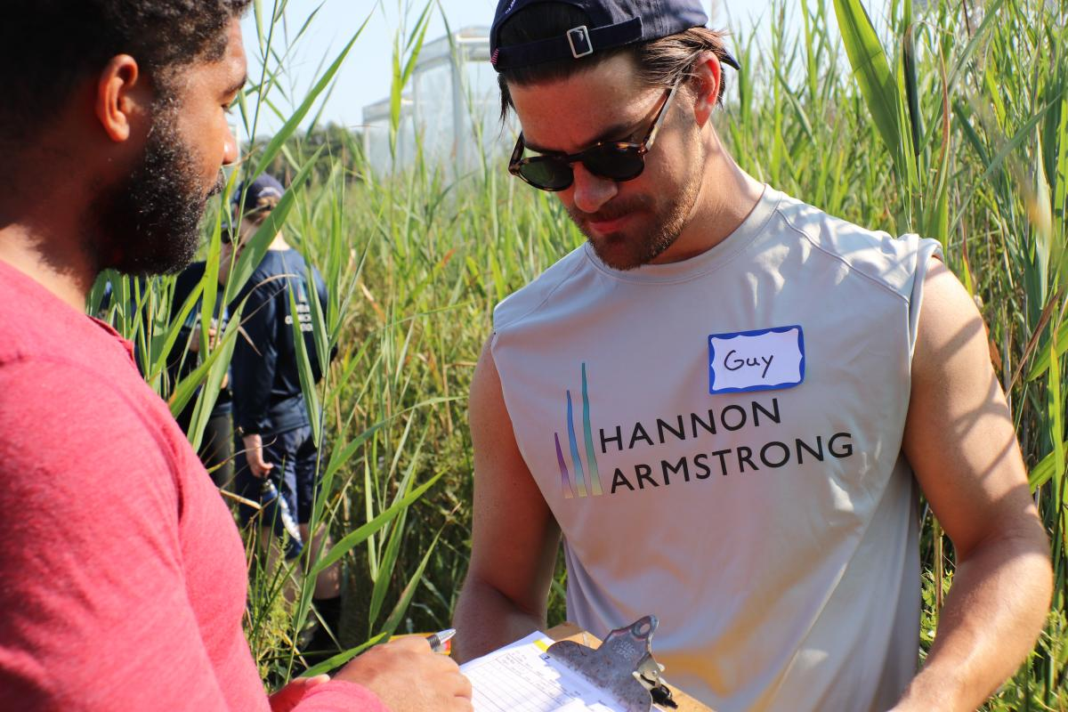 Man in Hannon Armstrong T-shirt looks at clipboard with SERC scientist
