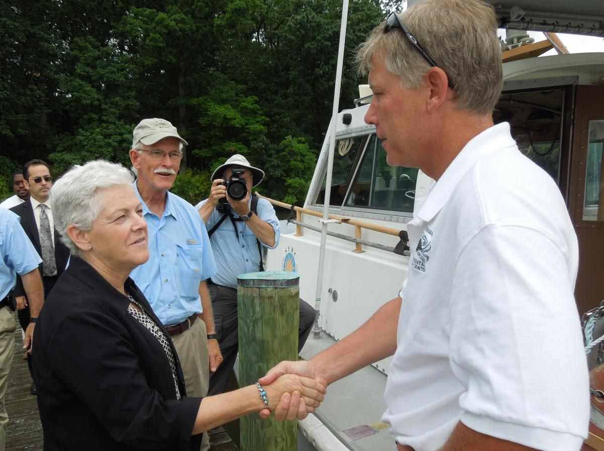 Female politician and boat captain shake hands