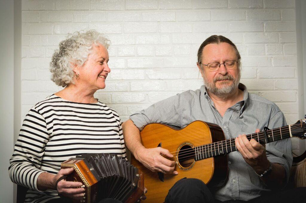 A woman playing accordion next to a man playing guitar