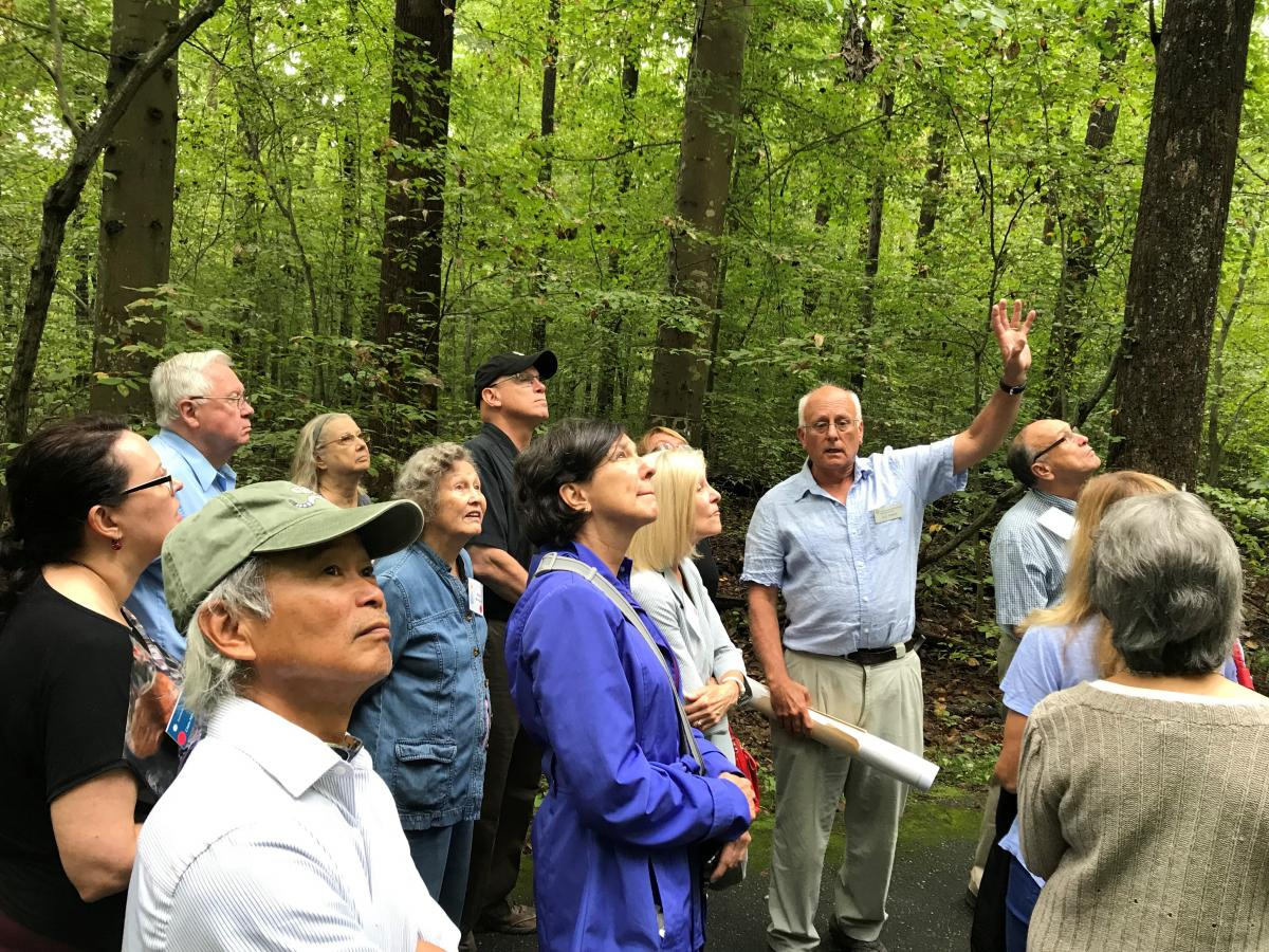 Scientist talking to group of visiting adults in a forest