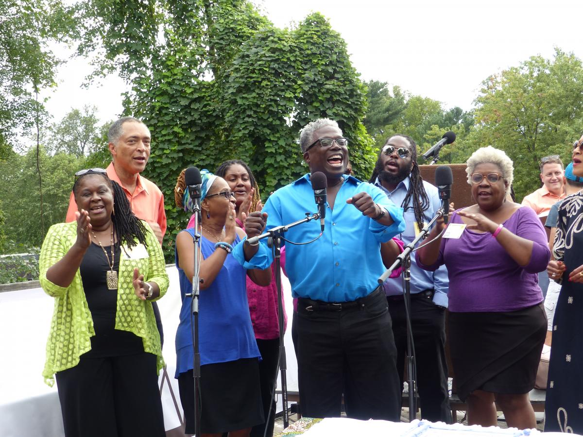 African-American choir singing beside a forest