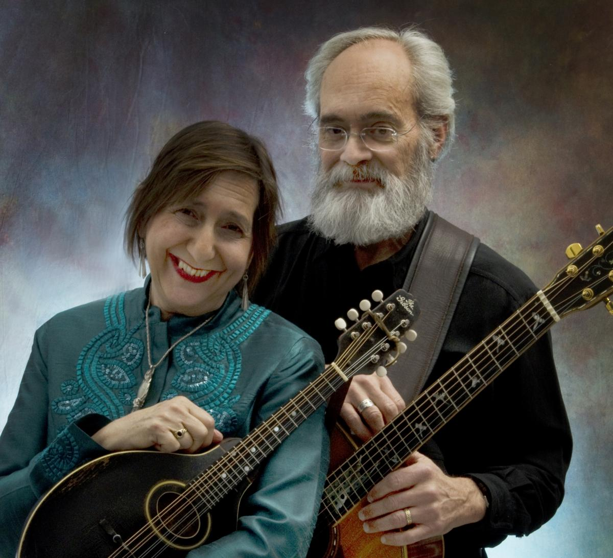 A woman and man standing together holding guitars