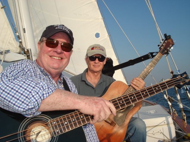 Two men on a boat with guitars
