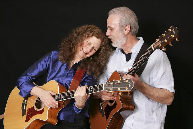 A woman and a man playing guitars together