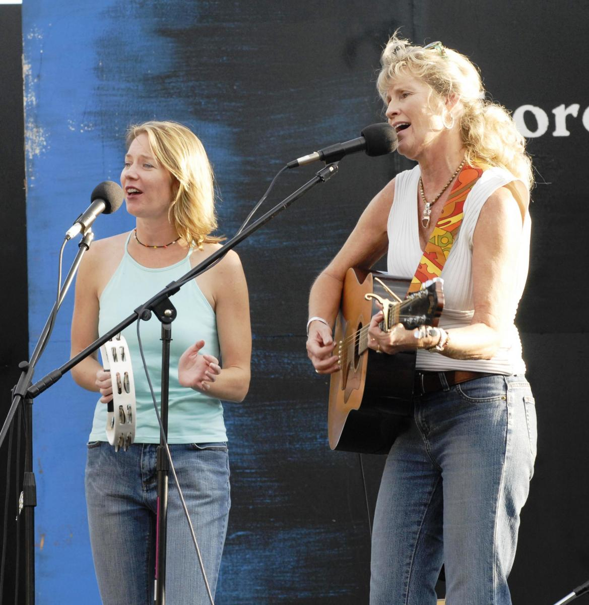 Two blonde women singing on stage with a tambourine and guitar