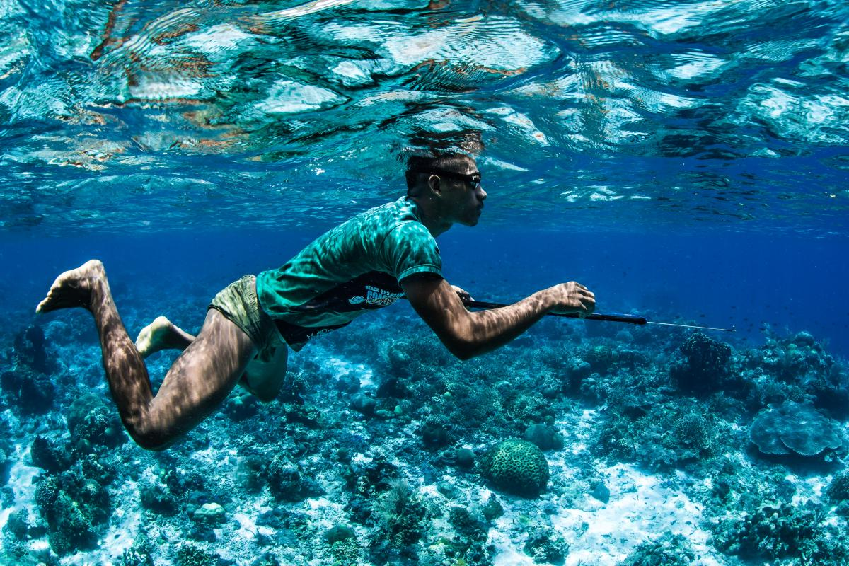 A young man in shorts and a T-shirt spearfishing underwater