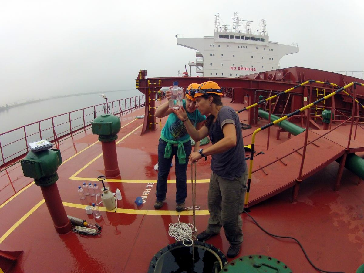 Two scientists inspect water sample on boat
