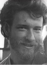 Black and white photo of young PhD student with curly hair and a beard