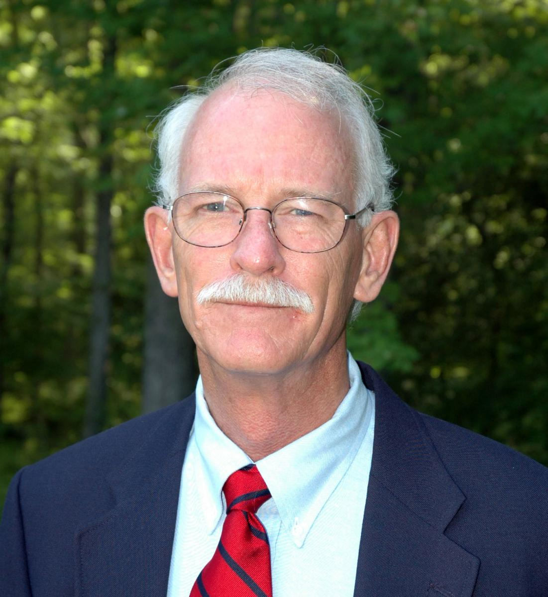 Tuck Hines in a navy suit, with white hair, mustache and glasses