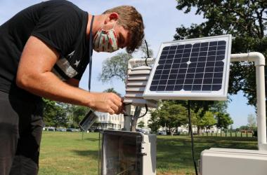 Young man with face mask standing over sensor with solar panel on grassy lawn