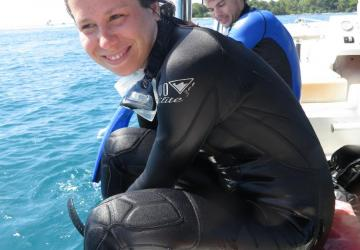 Sarah Gignoux-Wolfsohn, a young woman with dark hair, sits in a black wet suit on the edge of a boat