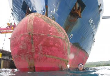 A diver gets ready to dive under the bulbous bow of a ship.
