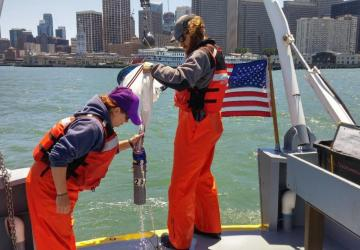 Field crew (Becca & Carl) pulling up a plankton net