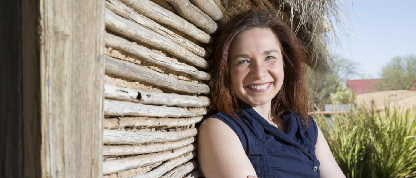 Katharine Hayhoe, a young woman with auburn hair, leans against the wall of a wooden shed