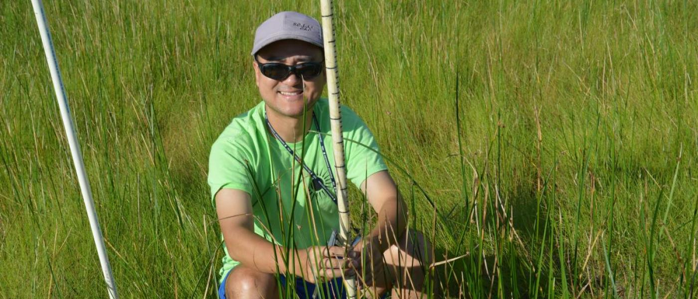 Young man in green T-shirt sitting in marsh with measuring stick