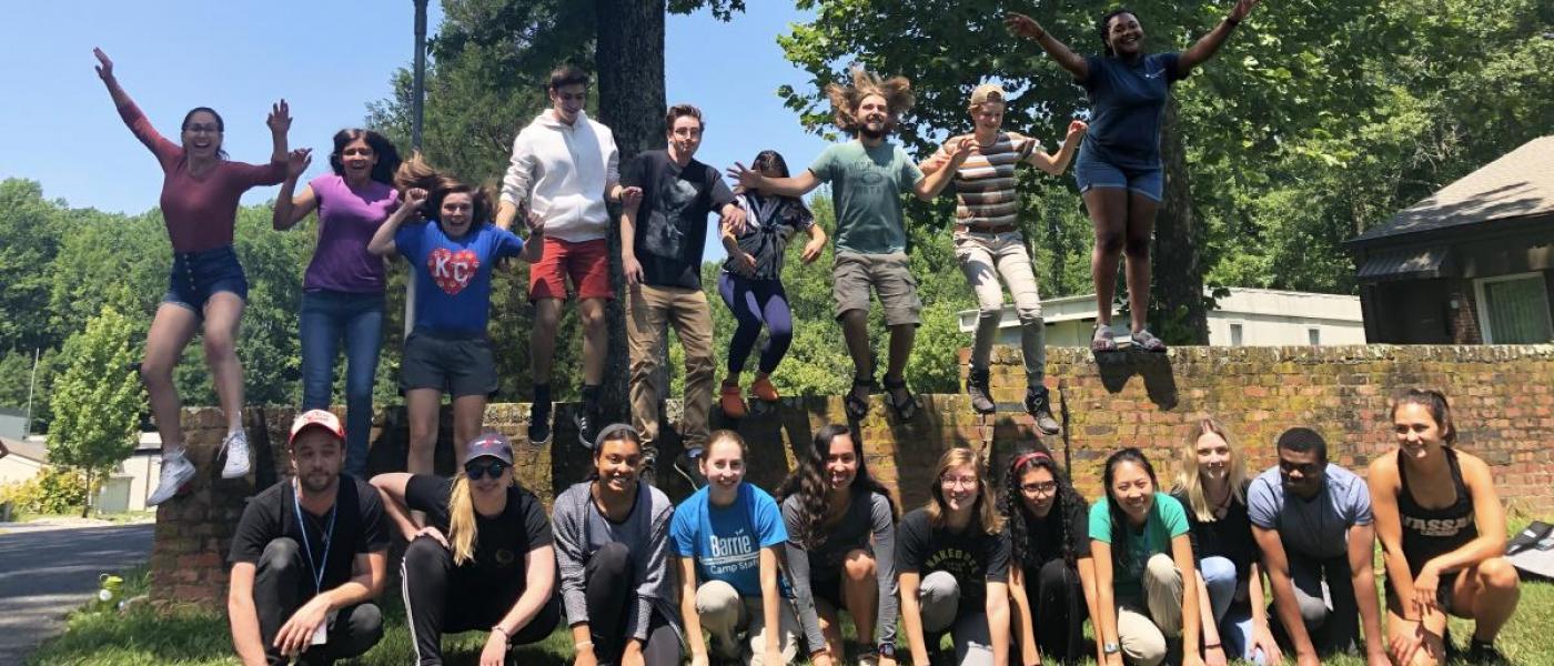 Nine interns jumping off brick divider, with eleven more kneeling in front