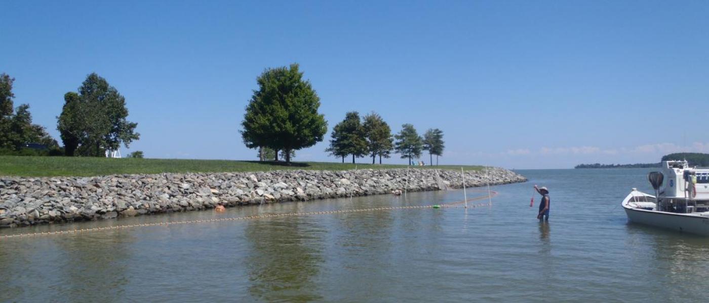 Boat beside rocky shoreline with riprap