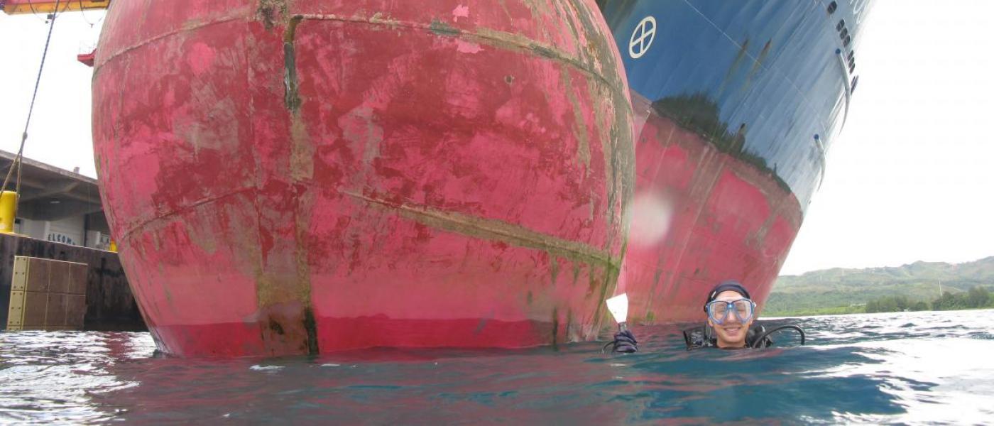 A diver next to a commercial ship