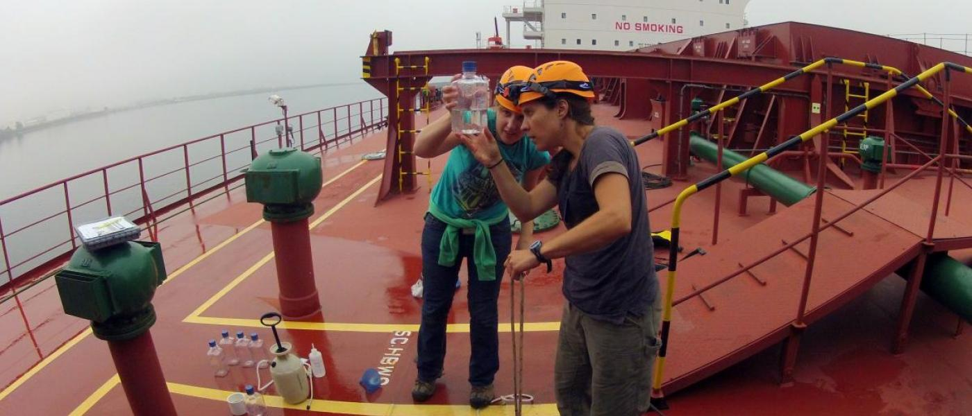 Two scientists inspect ballast water samples on ship
