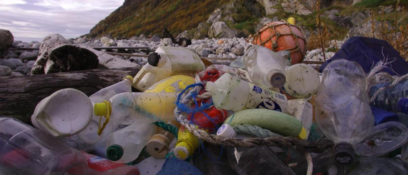 Pile of plastic bottles and other debris on a rocky beach