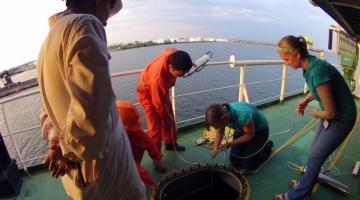 Drs. Jenny Carney and Katrina Lohan with crew members sampling ballast water
