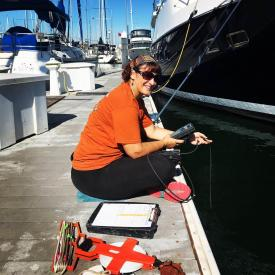 Scientist taking salinity measurements in a marina